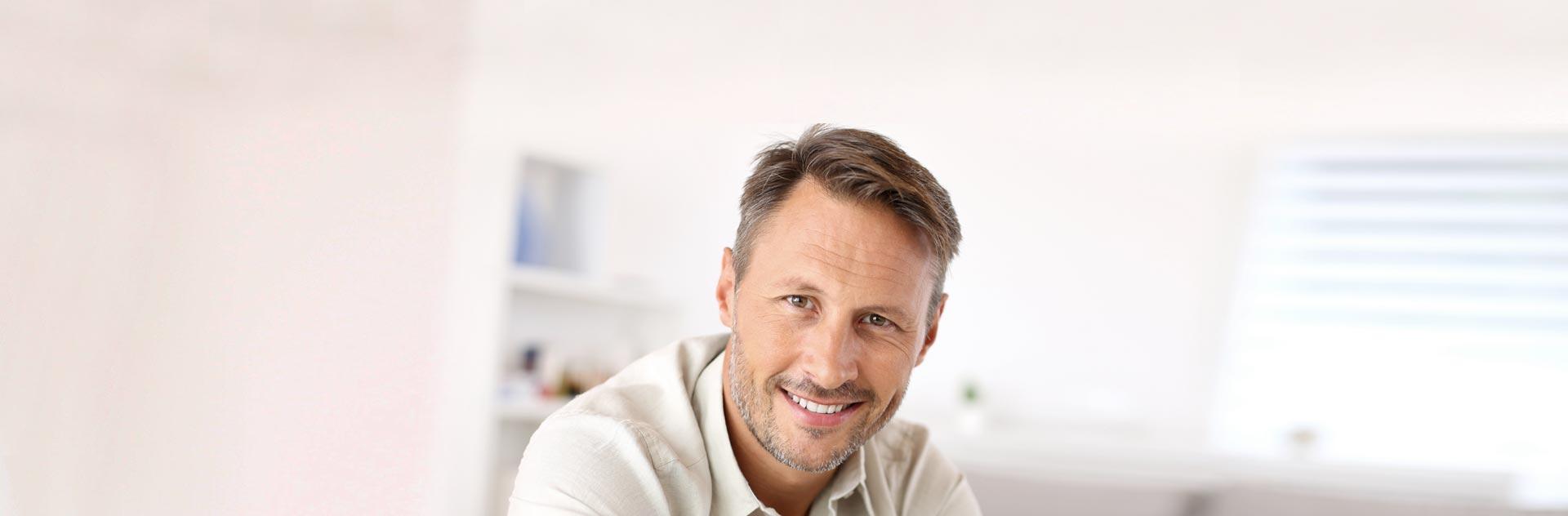 Hombre sonriendo tras optar por las Pelucas Estéticas de Capilárea
