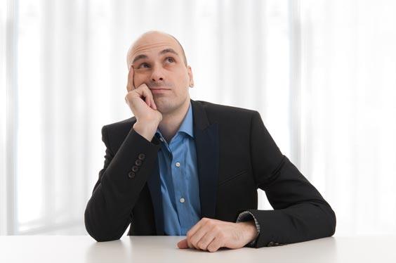 Imagen de hombre con falta de pelo preocupado por su futuro profesional
