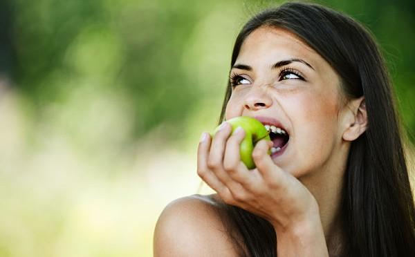 Mujer comiendo fruta, uno de los alimentos clave para el cabello